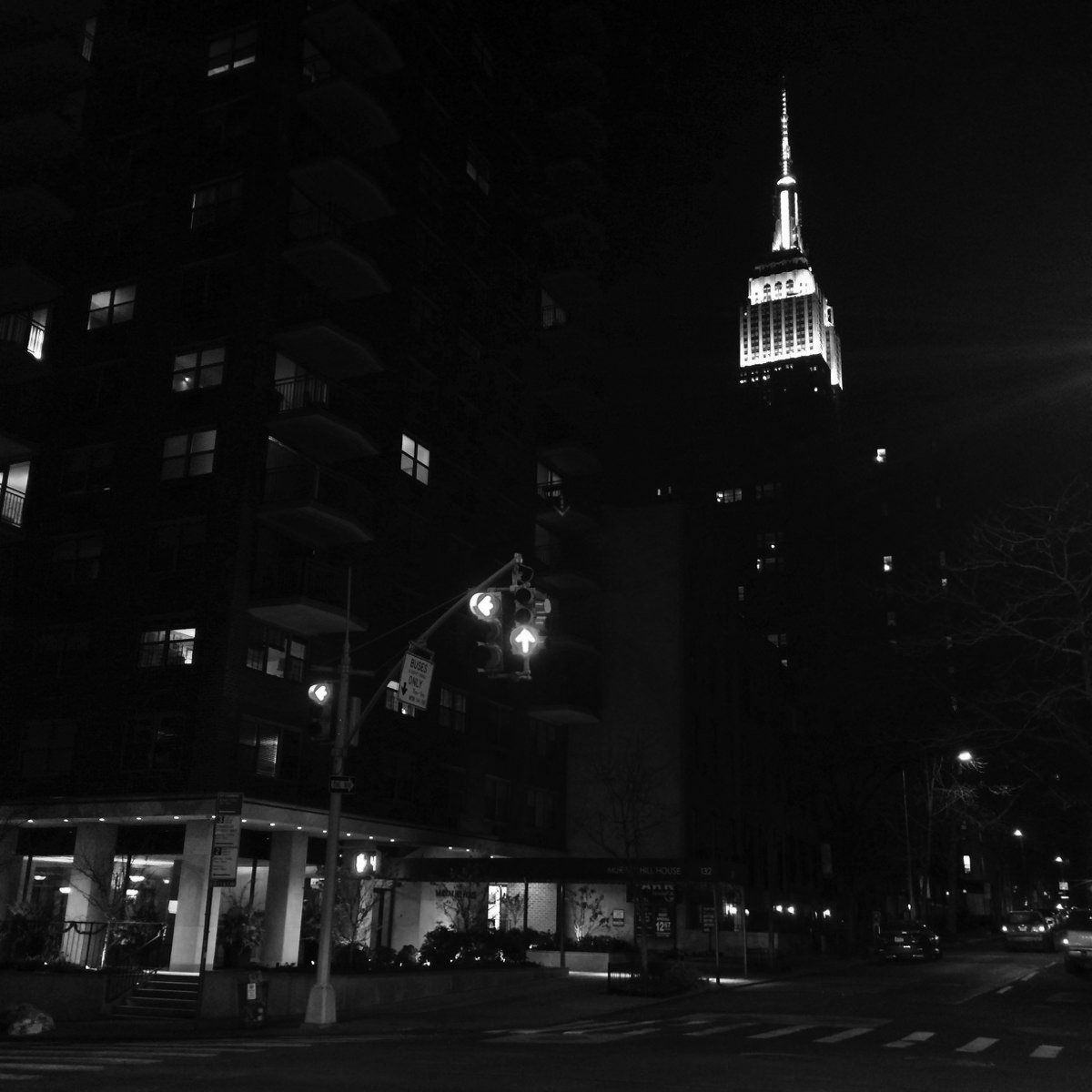 The top of the Empire State building lit up at night.
